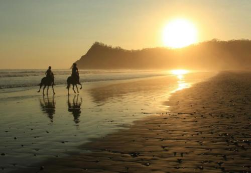 Horseback riding on the beach sunset Costa Rica